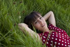 young woman, 25, lying in a meadow - stock photo