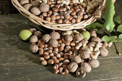 wicker basket with mixed nuts, walnuts (juglans regia), peanuts (arachis hypo - stock photo
