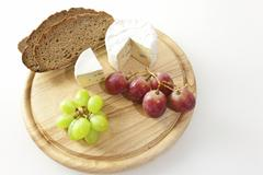 Blue cheese on a board with bread and grapes Stock Photos