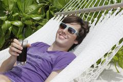 young man relaxing in a hammock, holding a drink, maldives, indian ocean - stock photo
