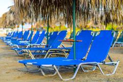 Beach sunbeds with straw umbrellas Stock Photos