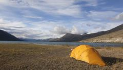 Stock Photo of tent on the shore of kusawa lake, mountains behind, yukon territory, canada