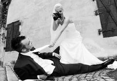 Bride photographing the groom with an old camera, photo shoot, wedding Stock Photos