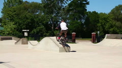 Stock Video Footage of Young man performing a radical bmx jump at skatepark