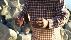 Man Balancing Rocks Along the Beach Stock Footage