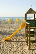 Early season, playground, slide, closed parasols on the sandy beach, adria, c Stock Photos