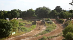 Motocross circuit with riders riding their dirt bikes Stock Footage