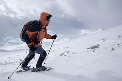snowshoe walker ascending neunerspitze peak, dolomites, south tyrol, italy, e - stock photo