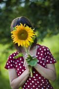 young woman, 25, holding a sunflower in front of her face - stock photo