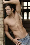 21-year-old mediterranean-looking man, wearing jeans, bare upper body, in cor - stock photo