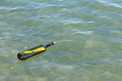Message in glass bottle in the sea Stock Photos