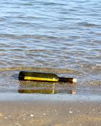 Treasure map in the bottle on the shore of the ocean Stock Photos