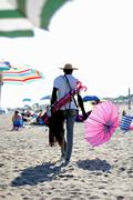African abusive salesman of umbrellas on the beach of the sea Stock Photos