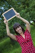 young woman, 25, holding a blackboard in her hands - stock photo