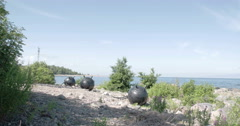 three big sea mines found on the rocky shore of the sea fs700 odyssey 7q 4k - stock footage