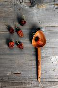 Chili peppers (capsicum) with a wooden spoon on a rustic wooden surface Stock Photos