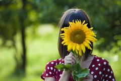 Stock Photo of young woman, 25, holding a sunflower in front of her face