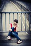 Stock Photo of desperate young woman sitting at a highway bridge
