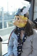 Young woman sitting in a public transport vehicle wearing an asterix mask Kuvituskuvat