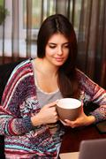 Attractive woman holding cup of coffee and looking at laptop Stock Photos