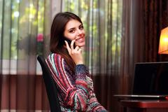 portrait of a smiling woman talking on the phone at home - stock photo