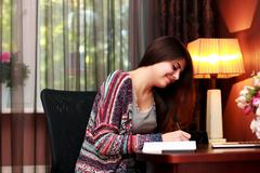 Happy female student doing homework at home Stock Photos