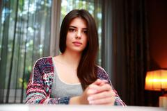 portrait of a serious woman sitting at the table at home - stock photo