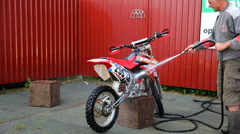 Motocross riders cleaning their dirt bikes Stock Footage