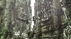 Huge stone faces on the walls of an ancient temple. cambodia, bayon Stock Footage