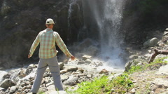 Male tourist standing at the foot of waterfall, water splashes - stock footage