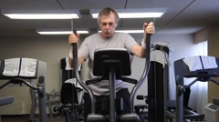 man exercising on an elliptical machine - stock footage