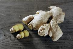 ginger (zingiber officinale) rhizome on a rustic wooden surface - stock photo