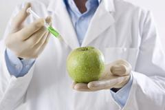 Man in a laboratory injecting liquid into an apple Stock Photos