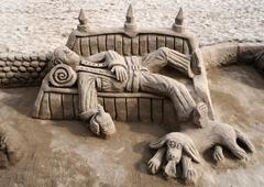 sand sculpture of a tramp with a dog lying on a bench - stock photo