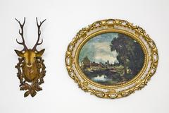 Plastic deer head and a kitschy oval, picture frame with a landscape motive Stock Photos