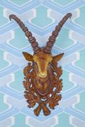 Plastic head of an ibex mounted on kitschy wallpaper from the 1960s or 1970s, Kuvituskuvat