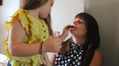 Little girl puts lipstick on mammy Stock Footage