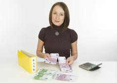 Young woman with bank receipts and money Kuvituskuvat