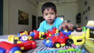 Stock Video Footage of Asian Boy Plays With His Toys At The Table