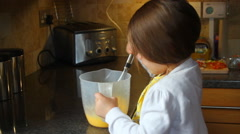 Little girl whisking eggs in a jug Stock Footage