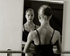 Girl dancing ballet at a bar in front of a mirror Stock Photos