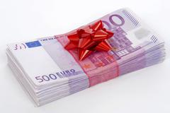 wad of 500 euro banknotes with red bow, symbolic of money gift - stock photo