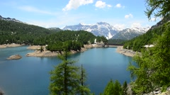 Alpine Lake Reservoir on a background of snow-capped peaks Stock Footage