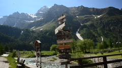 Italian Alps. Signpost. Bridge across the mountain river, the green valley and t Stock Footage
