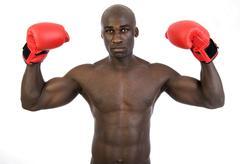 dark-skinned, athletic man, 30, wearing boxing gloves - stock photo