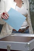 Woman putting her vote into the voting box Kuvituskuvat