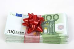 wad of 100 euro banknotes with red bow, symbolic of money gift - stock photo