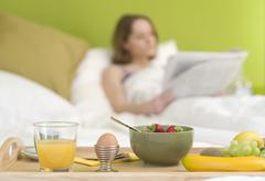 young woman, 25+, with a newspaper and breakfast in bed - stock photo
