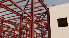 Metal construction building and construction worker Stock Footage