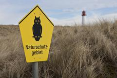 "sign ""naturschutzgebiet"" nature reserve, the lighthouse list-west at back, na - stock photo"